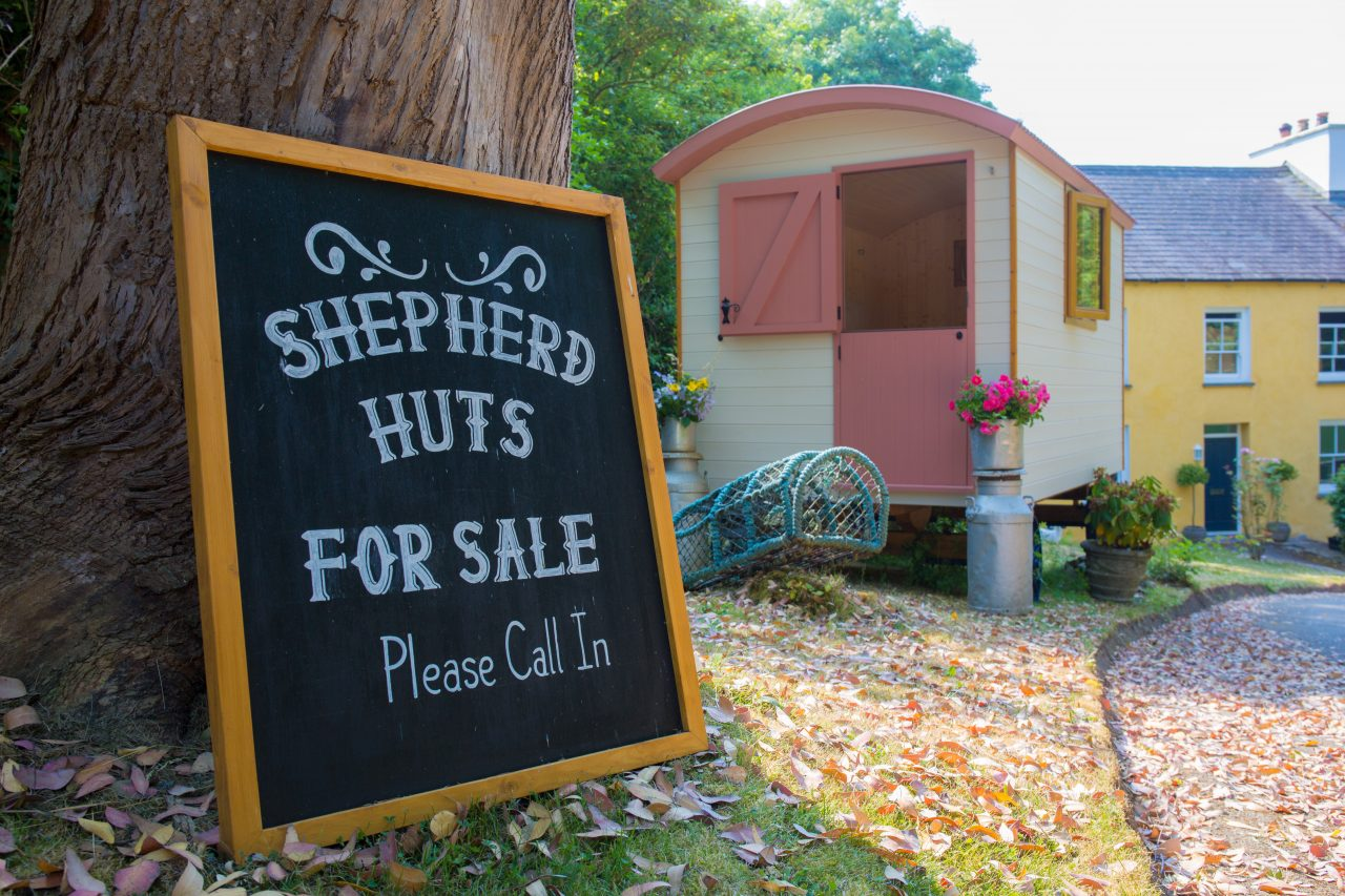 Shepherd hut with sign 'Shepherd Huts for sale, please call in'.