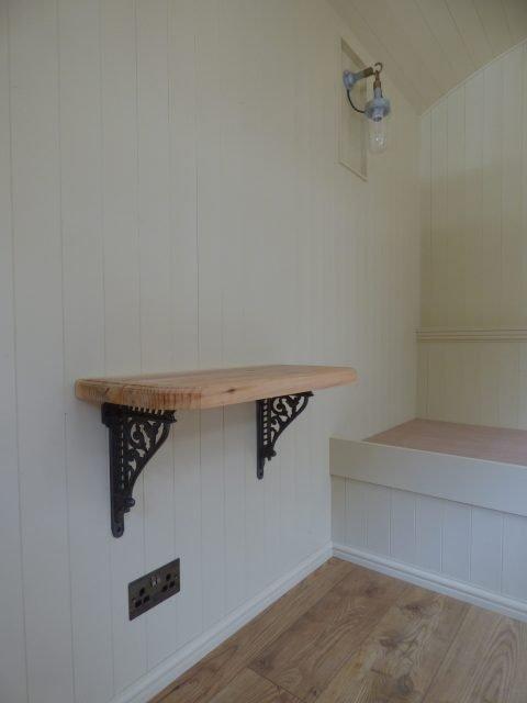 Handmade oak shelf inside shepherd hut