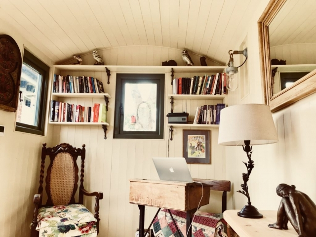 Old style writer's table and chair inside a shepherd's hut