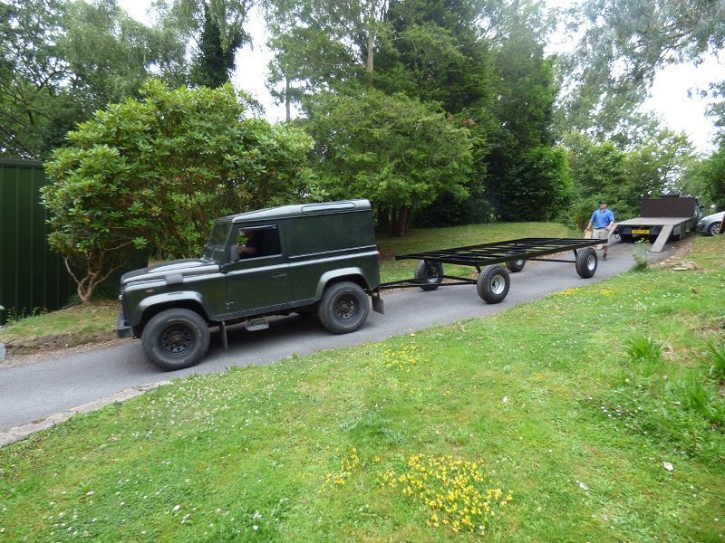 Shepherd hut chassis being towed by landrover