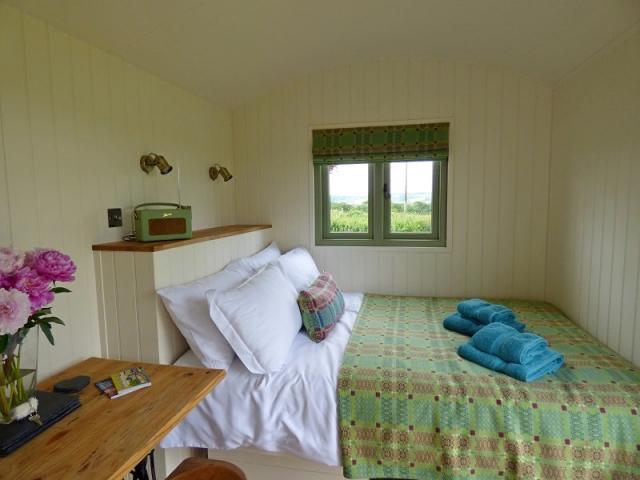 Double bed in handmade shepherd's hut