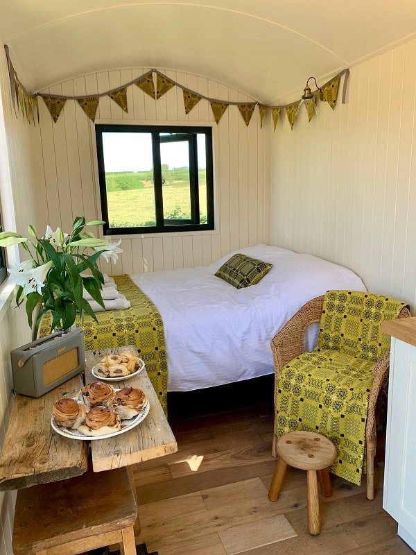 Bespoke Shepherd Hut with window view, bed, armchair and table with pastries