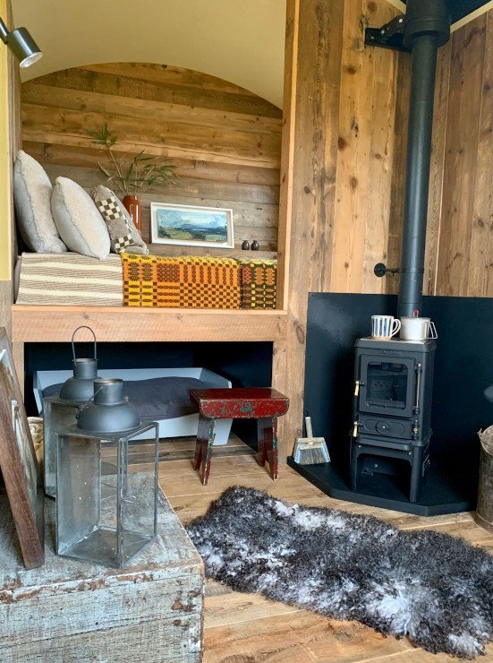 Hut with log burner and natural wood interior cladding