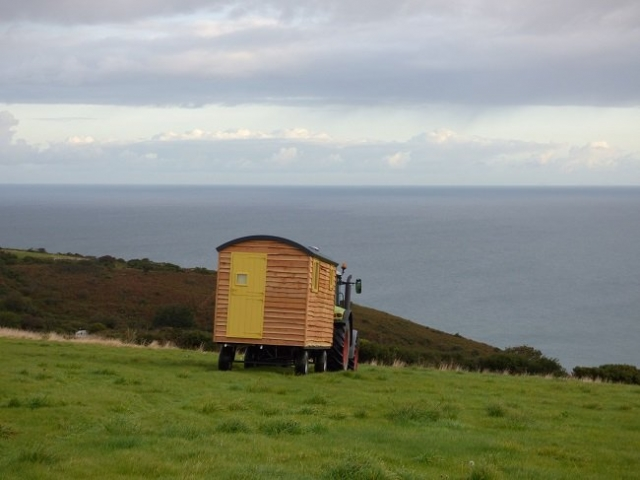 Bespoke shepherd hut being pulled by tractor over field with view over the sea