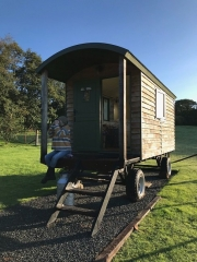 Bespoke shepherd hut with lady sitting in overhanging porch dangling legs over the edge