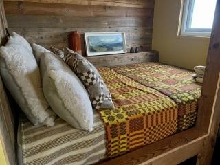 Beautiful bed and oak panelling in bespoke shepherd hut
